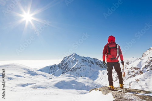 Fototapeta Mountaineer looking at a snowy mountain landscape