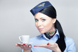 Young attractive stewardess holding a cup of coffee