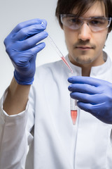 Chemiker träufelt eine rote Flüssigkeit in ein Reagenzglas