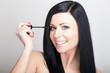 Attractive young woman using mascara makeup