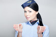 Attractive stewardess performing preflight safety demonstration