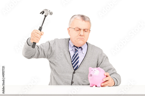 Angry mature man trying to break a piggy bank with a hammer