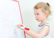 Pretty little girl writing with red marker on a whiteboard