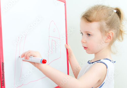 Pretty little girl drawing with red marker on a whiteboard