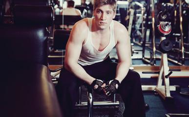 Homme assis au milieu d'appareils de musculation