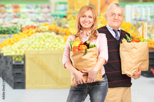 Man and woman in a supermarket holding paper bags