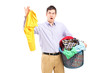 Man holding a smelly blouse and a laundry basket