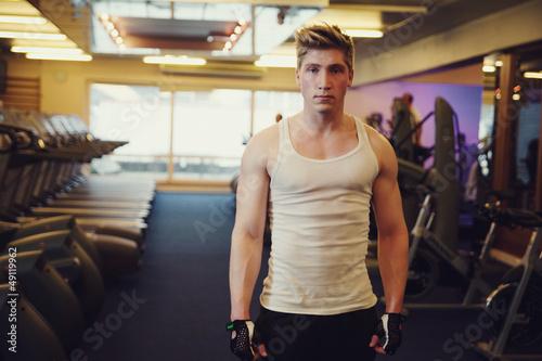 Homme au milieu d'une allée d'appareils de fitness