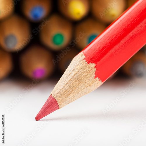 red pencil draws or writing on paper sheet, colored pencils as b