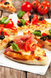 Pizza with ham, pepper and olives on old wooden background