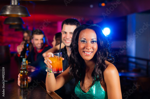 People with cocktails in bar or club
