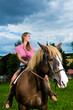 Young woman riding the horses on the meadow