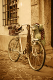 Vintage bicycle leaning against an old door in a medieval street - 49122900