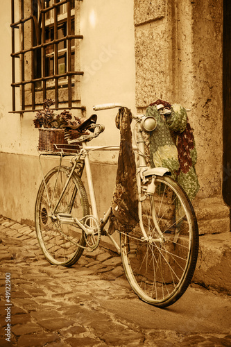 Aluminium Fiets Vintage bicycle leaning against an old door in a medieval street