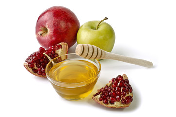 Apples, pomegranate and bowl of honey