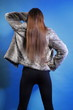 young woman in fur long hair blue background
