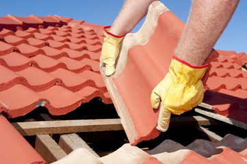 Construction worker tile roofing repairs