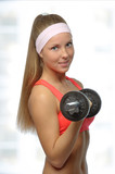Image of blonde smiling woman with barbell in hand