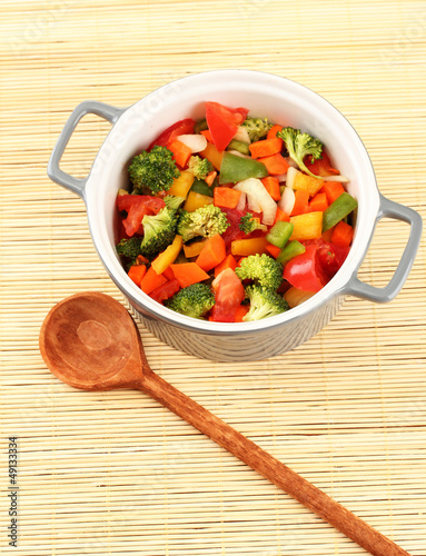 Vegetable stew in gray pot on bamboo mat background
