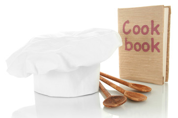 Chef's hat with spoons and cook book isolated on white