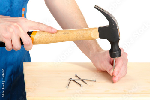 Builder hammering nails into board isolated on white