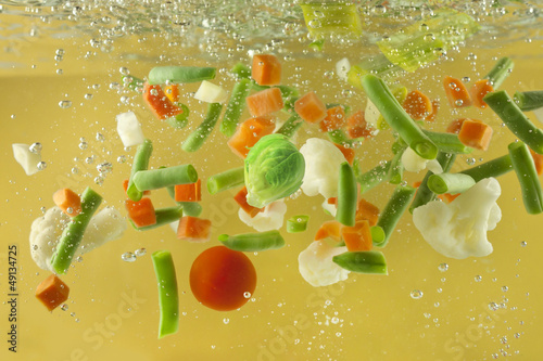 Vegetables splash in water soup cooking concept