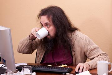 Nerd schaut konzentriert auf Monitor und trinkt aus Tasse