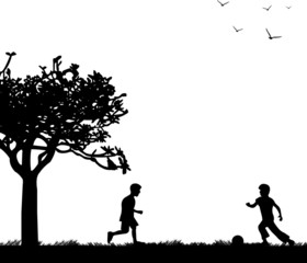 Little boys playing with ball on spring field silhouette