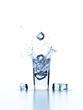 Eiswürfel fallen in ein Glas