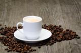 kaffeetasse mit bohnen auf holzbrett