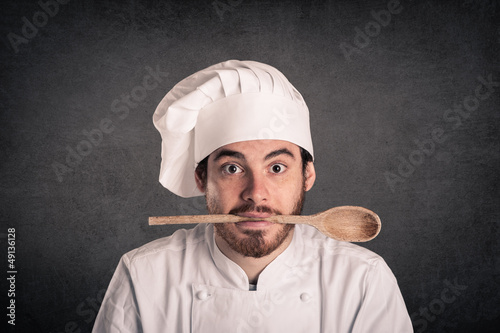 Funny portrait of a young cook man with scoop and uniform
