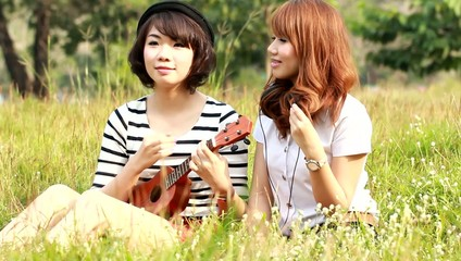 Two beautiful girl sits on a meadow with an ukulele