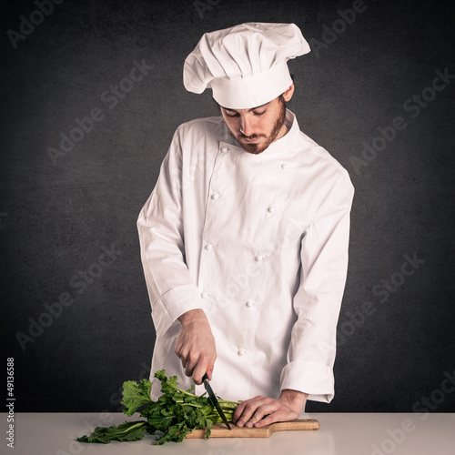 Young cook man with uniform cutting vegetables
