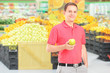 Man standing in a supermarket and holding an apple