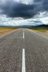 An empty desert road with dark and foreboding storm clouds