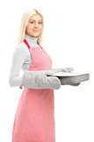 Young woman wearing cooking mittens and apron holding a baking t