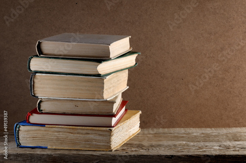 Pile of old books on wooden table