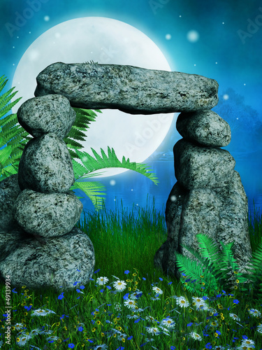 Kamienny łuk na łące z kwiatami i paprocią