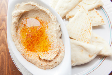 Creamy hummus topped with olive oil served with pita bread