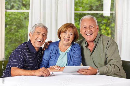 Lachende Senioren mit Tablet PC