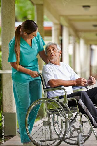 Krankenschwester redet mit Mann im Rollstuhl