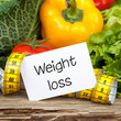 Gemüse auf Holz mit Massband und Zettel WEIGHT LOSS