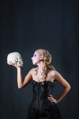 Woman with a skull, studio shot.