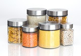 Fototapety Food ingredients in glass jars, on white background