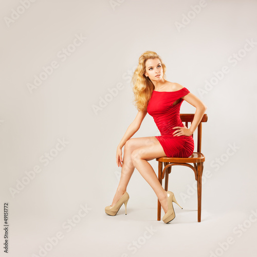 Beautiful Woman in Red Dress Sitting on a Chair