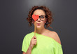woman in glasses cover one eye with red heart