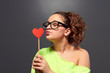 young woman in glasses kissing paper heart