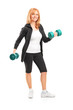 Full length portrait of a mature woman lifting up dumbbells