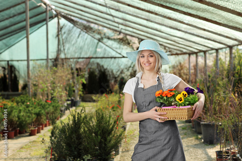 Female gardener posing with a basket full of flowes in a hothous
