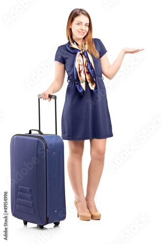 Full length portrait of a young woman with a suitcase